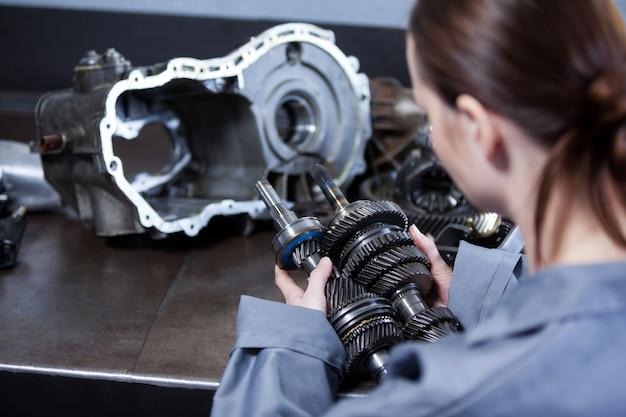 Weibliche mechaniker mit ersatzteilen