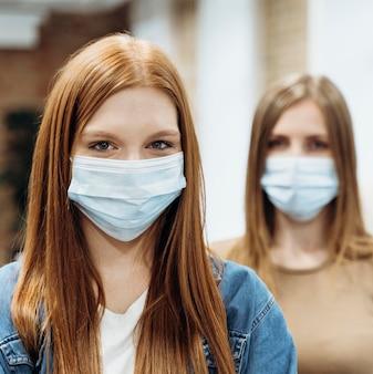 Weibliche mitarbeiter, die medizinische masken bei der arbeit tragen