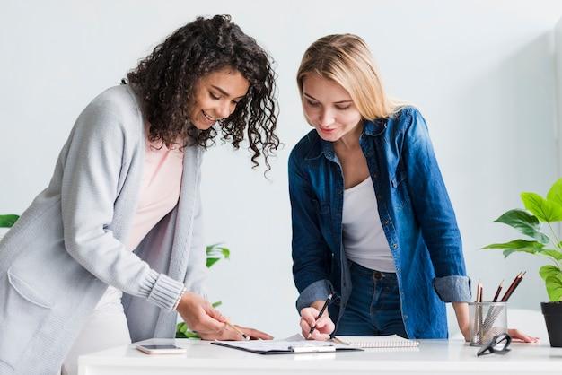 Weibliche mitarbeiter, die über dem schreibtisch bespricht projekt sich lehnen