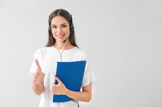 Weibliche mitarbeiterin des technischen supports, die eine daumen-hoch-geste auf grau zeigt