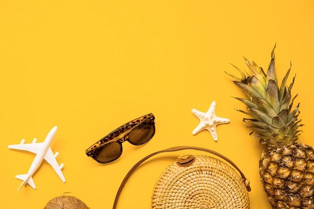 Weibliche mode-ausstattungs-ebenenlage des bunten sommers. strohbeutel, sonnenbrille, kokosnuss, ananashintergrund
