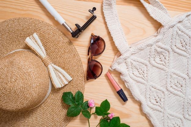 Weibliche mode-ausstattungs-ebenenlage des bunten sommers. strohhut, bambustasche, sonnenbrille, draufsicht, kopienraum, breite zusammensetzung. sommermode, urlaub