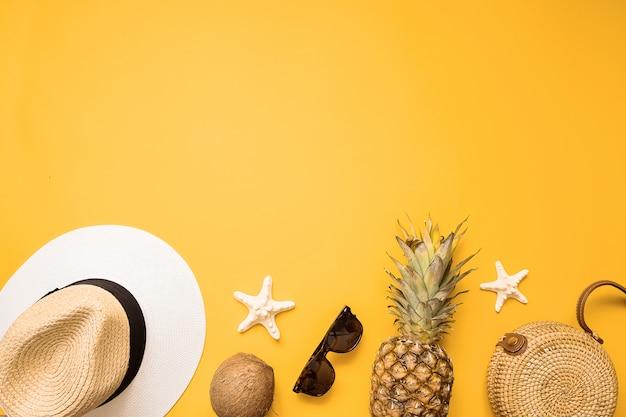 Weibliche mode-ausstattungs-ebenenlage des bunten sommers. strohhut, bambustasche, sonnenbrille, kokosnuss, ananas