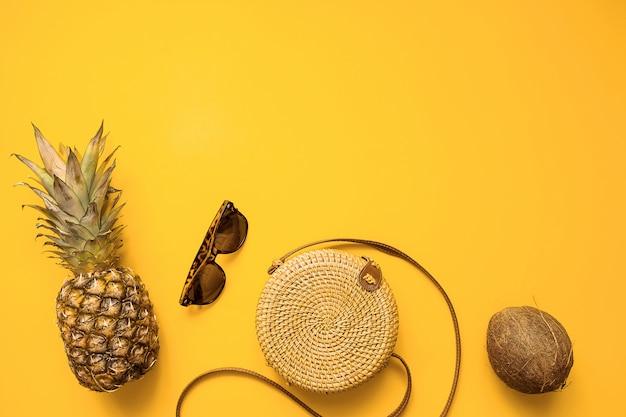 Weibliche mode-ausstattungsebenenlage des bunten sommers mit bambustasche, sonnenbrille, kokosnuss, ananas