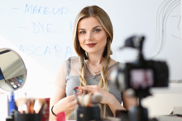 Weibliche mode vlogger broadcast beauty video blog. junge blonde frau, die inhalt notiert. schönes mädchen mit zöpfen frisur. maskenbildner-aufnahme-haar-sorgfalt-führer durch digitalkamera