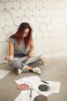 Weibliche modedesignerin, die an einem laptop in ihrem studio arbeitet, das stoffe und skizzen prüft, die auf boden sitzen. kreativwirtschaft.