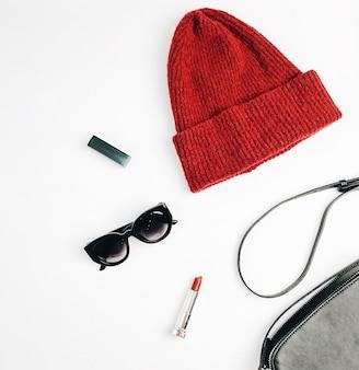Weibliche modekleidung und accessoires auf weißem hintergrund. roter hut, schwarze handtasche, sonnenbrille, lippenstift und leggings. flache lage, ansicht von oben