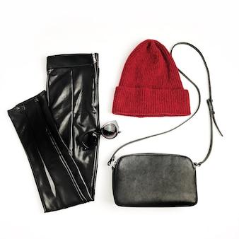 Weibliche modekleidung und accessoires auf weißem hintergrund. roter hut, schwarze handtasche, sonnenbrille und leggings. flache lage, ansicht von oben
