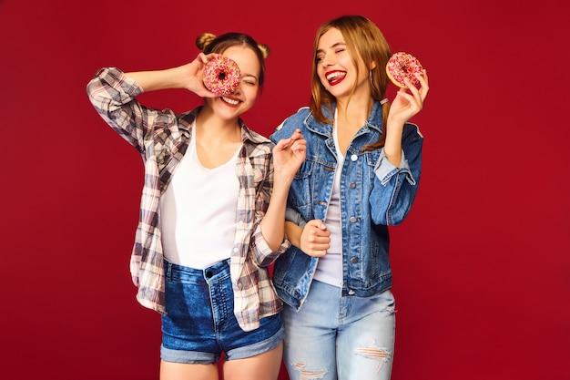 Weibliche modelle, die rosa donuts mit streuseln halten