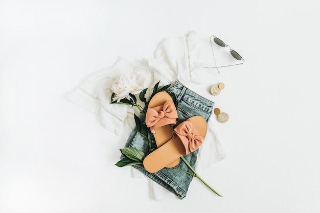 Weibliche modeoberfläche mit weißer pfingstrosenblume, hausschuhen, sonnenbrille, ohrringen, shorts, t-shirt