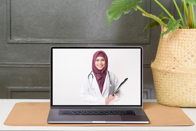 Weibliche muslimische ärztin, die einen videoanruf im sozialen netzwerk mit patientenberatung über gesundheitsprobleme tätigt.