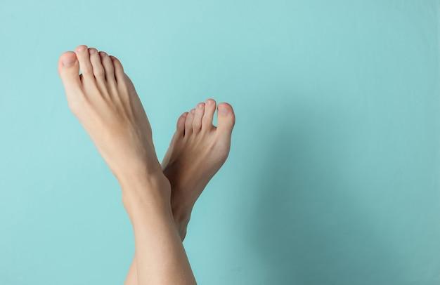 Weibliche nackte füße auf einem blauen hintergrund