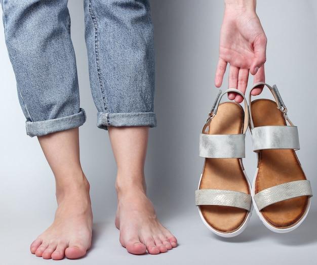 Weibliche nackte füße in jeans und sandalen in ihren händen auf weiß.