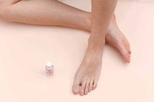 Weibliche nackte füße, nagellackflasche auf beigem hintergrund. schönheitspflegekonzept
