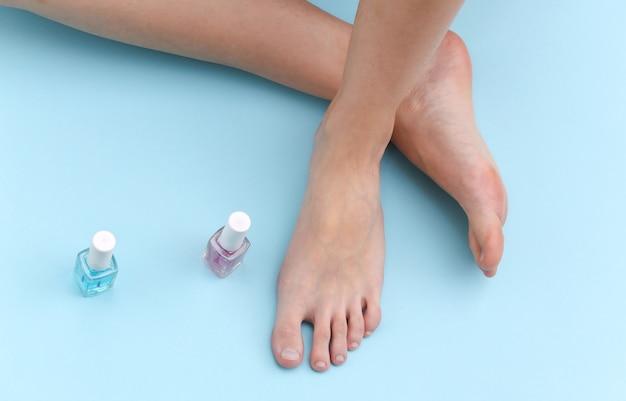Weibliche nackte füße, nagellackflasche auf blauem hintergrund. schönheitspflegekonzept