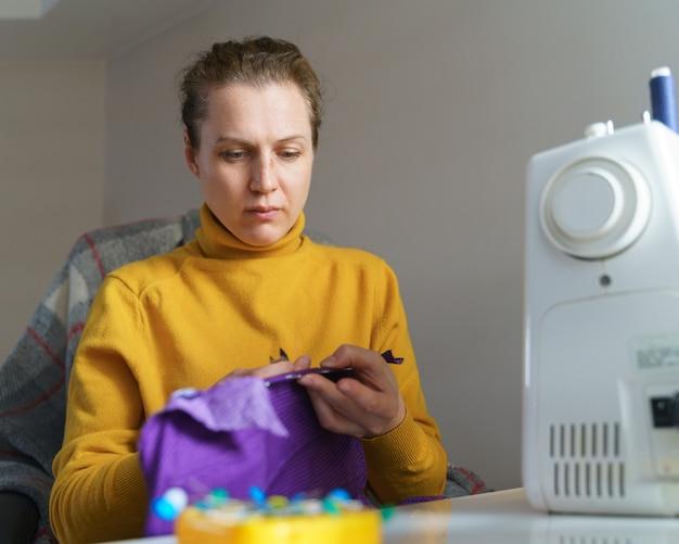 Weibliche näherin, die korsett näht, während sie zu hause an ihrem kreativen arbeitsplatz sitzt