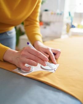 Weibliche näherin, die schnittmuster macht, während sie an ihrem kreativen arbeitsplatz arbeitet