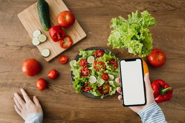Weibliche nahrungsmittelbloggerin, die zu hause mit smartphone strömt