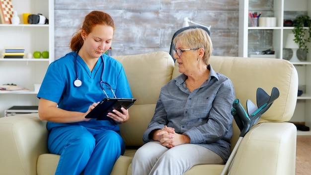Weibliche nuse, die älteren älteren rentnern hilft, ihren tablet-computer im pflegeheim zu benutzen