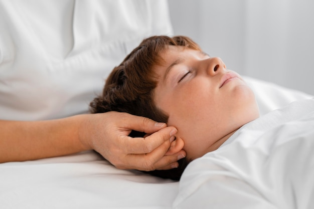 Weibliche osteopathin, die ein kind behandelt, indem sie seinen kopf massiert