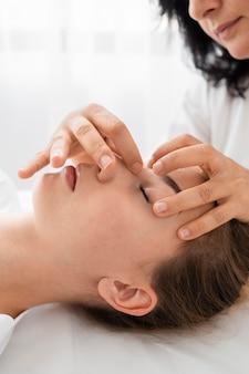Weibliche osteopathin, die eine patientin behandelt, indem sie ihr gesicht massiert