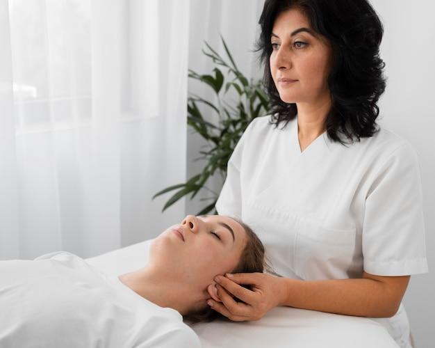 Weibliche osteopathin, die einen patienten drinnen behandelt