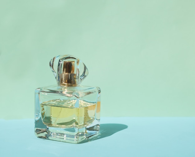 Weibliche parfümflasche auf einem pastellblauen hintergrund mit kristallschatten