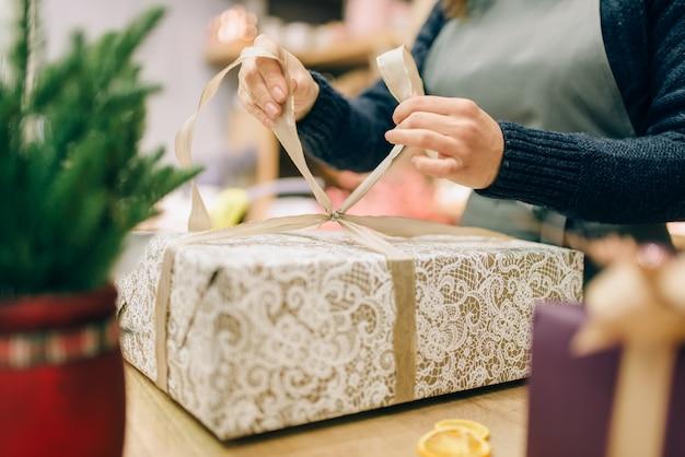 Weibliche person bindet eine goldene schleife auf geschenkbox, handgemachte verpackung und dekorationsprozess. frau wickelt geschenk auf dem tisch, dekorverfahren ein