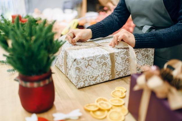 Weibliche person bindet eine goldene schleife auf geschenkbox
