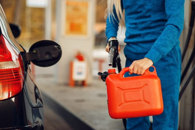 Weibliche person, die kanister an tankstelle füllt, kraftstoff nachfüllen. benzintanken, benzin- oder dieseltankservice, benzintanken