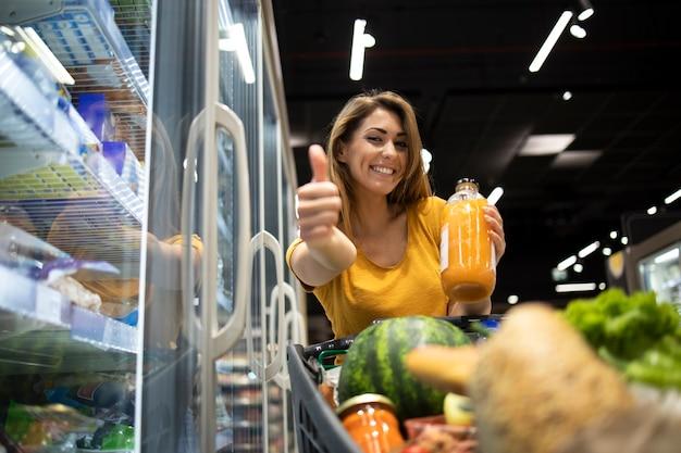 Weibliche person, die orangensaft im lebensmittelgeschäft hält und daumen hoch zeigt