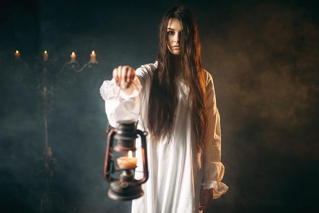 Weibliche person hält petroleumlampe, dunkle magie