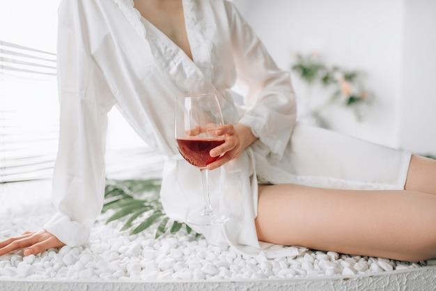 Weibliche person im weißen bademantel, der am rand des bades mit glas rotwein sitzt. badezimmerinnenraum mit fenster