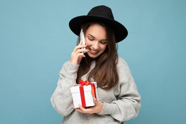 Weibliche person lokalisiert über blaue hintergrundwand, die schwarzen hut und grauen pullover hält, der geschenkbox hält, der auf handy spricht.