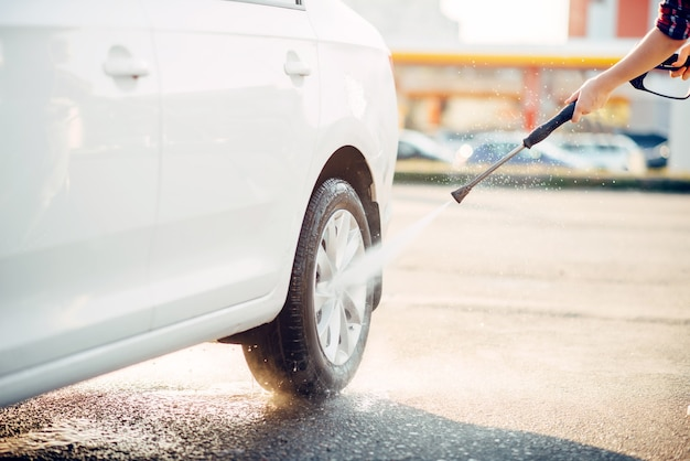Weibliche person reinigt autoräder mit hochdruckwasserpistole. junge frau auf selbstbedienungsautowaschanlage. waschen des fahrzeugs im freien am sommertag