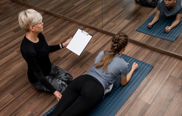 Weibliche personal trainerin hilft ihrem kunden hohe sicht