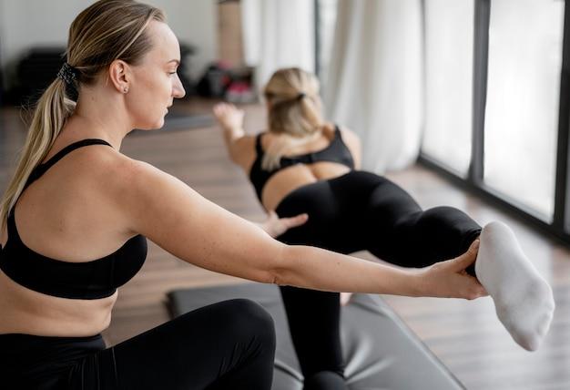 Weibliche personal trainerin hilft ihrem kunden