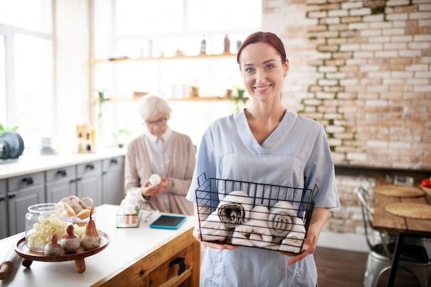 Weibliche pflegekraft, die sich nach dem waschen der handtücher zufrieden fühlt