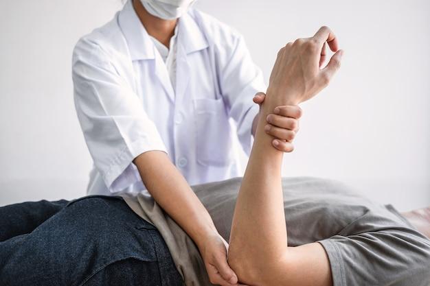 Weibliche physiotherapeutin, die die behandlung des verletzten arms des männlichen athleten des athleten, das dehnen und das training untersucht, die schmerzen der rehabilitationstherapie in der klinik macht.