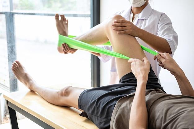 Weibliche physiotherapeutin, die verletztes bein des männlichen patienten behandelt