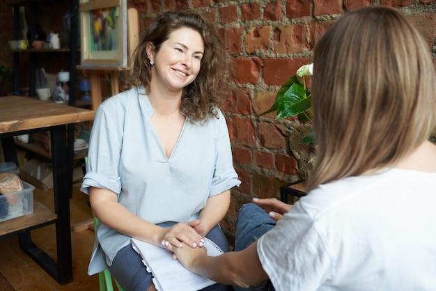 Weibliche psychologin, die hand der frau hält