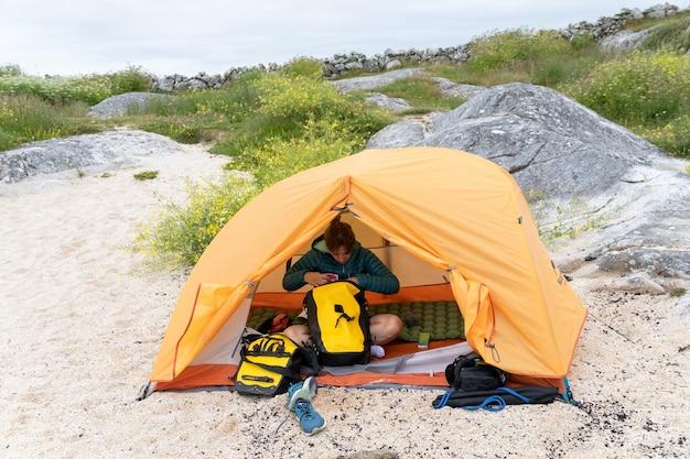 Weibliche radfahrerreisende in einem zelt, die ihre kleidung organisieren und am strand kostenlos campen?