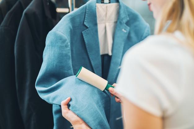 Weibliche reinigungskraft in der wäscherei, die saubere kleidung überprüft und fussel mit rolle entfernt.