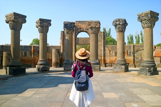 Weibliche reisende beim besuch der kathedrale von zvartnots, unesco-weltkulturerbe in der armenischen provinz armavir