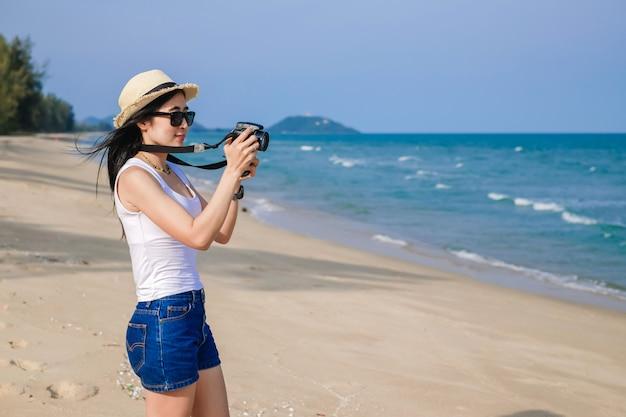 Weibliche reisende, die am strand steht und foto für blick auf das meer im urlaub macht.