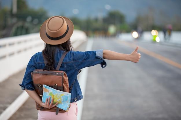 Weibliche reisende, die autos auf der straße wellenartig bewegen