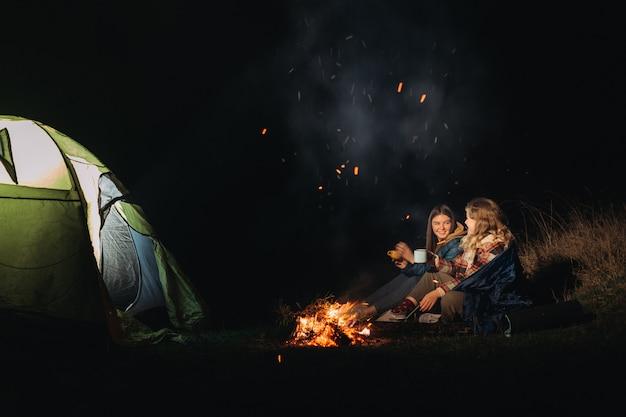 Weibliche reisende, die nahe lagerfeuer sitzen