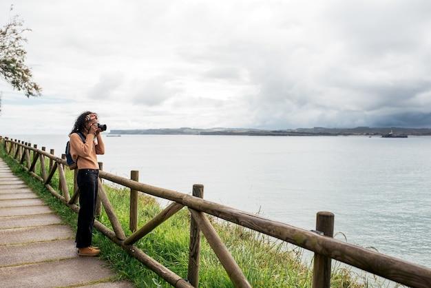 Weibliche reisende in freizeitkleidung, die das plätschernde meer fotografiert?