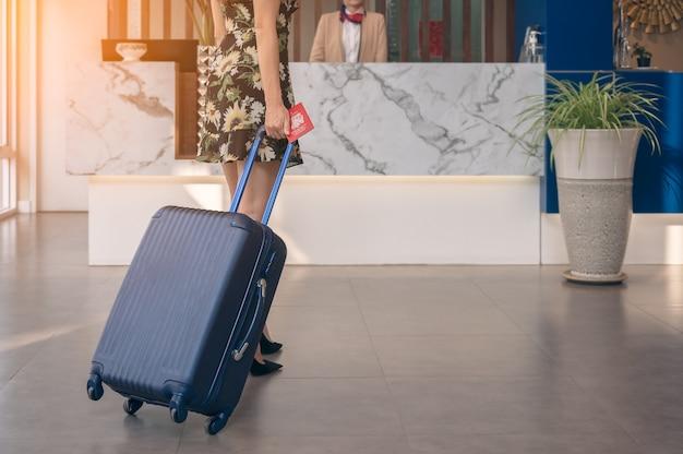Weibliche reisende mit gepäck zu fuß zum check-in-schalter des hotels