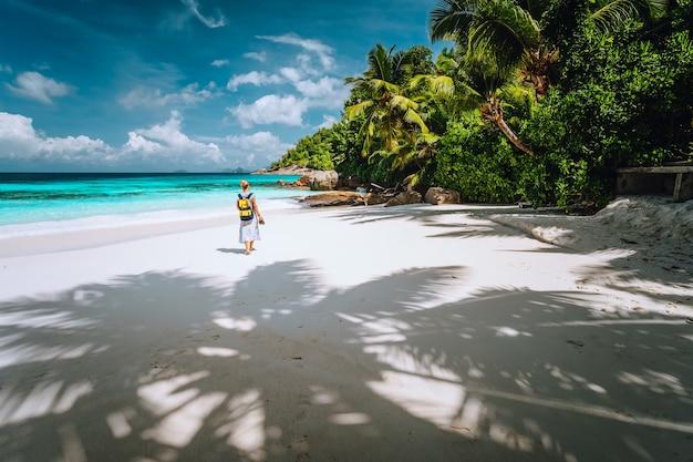 Weibliche reisetouristen genießen tropischen epischen strand mit palmen und blauem ozean luxusparadies-erholungsurlaubskonzept.